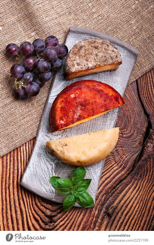 Käse und schwarze Trauben auf handgemachter Tonwarenplatte Lebensmittel Milcherzeugnisse Frucht Teller Tisch Holz Rost frisch lecker oben Keramik