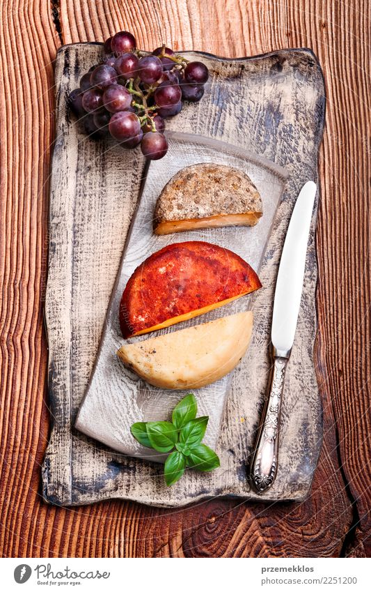 Käse und schwarze Trauben auf handgemachter Tonwarenplatte Lebensmittel Frucht Frühstück Mittagessen Teller Tisch Holz Rost frisch lecker oben Keramik