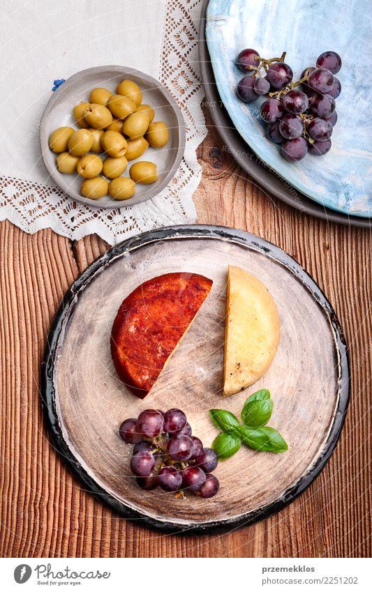 Käse und schwarze Trauben auf handgemachter Tonwarenplatte Lebensmittel Frucht Ernährung Frühstück Teller Tisch Holz Rost frisch lecker oben Keramik