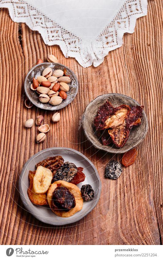 Trockenfrüchte und Nüsse in handgemachten Tonwarenschüsseln Lebensmittel Frucht Dessert Schalen & Schüsseln Tisch Holz Rost lecker oben Keramik getrocknet