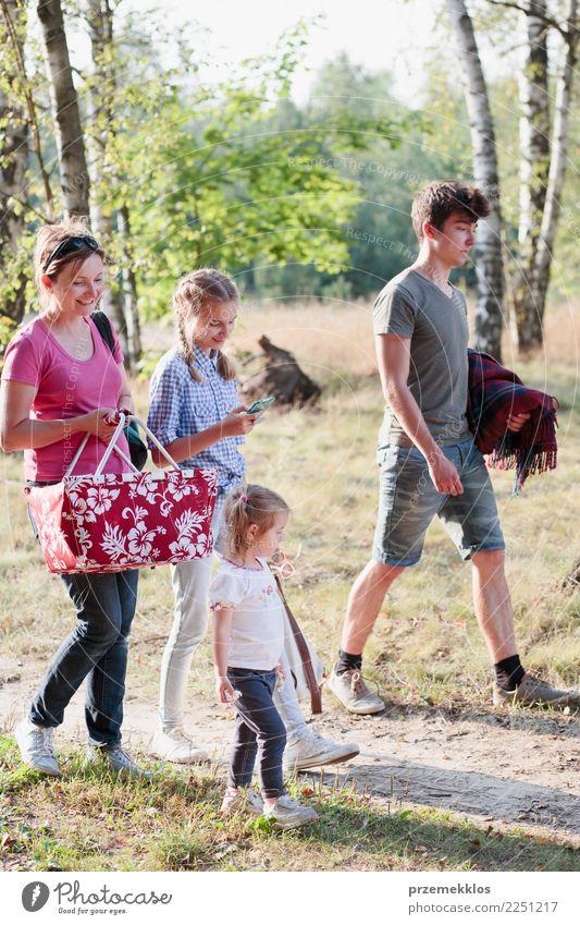 Familie, die auf Picknick zum Wald am sonnigen Tag geht Kind Mensch Natur Ferien & Urlaub & Reisen Jugendliche Junge Frau Pflanze Sommer Landschaft Baum