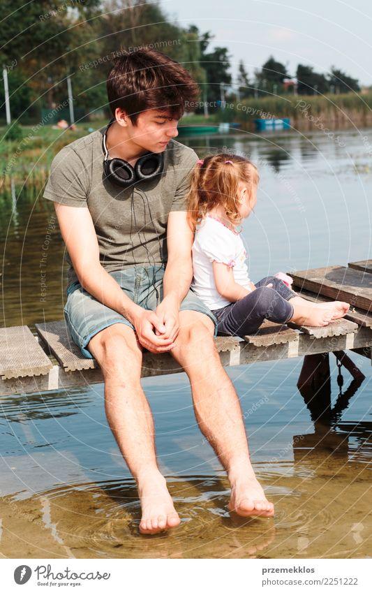Junge und seine kleine Schwester sitzen auf einem Steg über dem See und tauchen an sonnigen Sommertagen die Füße ins Wasser Lifestyle Freude Glück Erholung