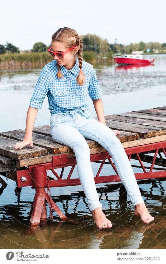 Mädchen, das auf Anlegestelle über dem See sitzt und Füße im Wasser eintaucht Lifestyle Freude Glück Erholung Freizeit & Hobby Ferien & Urlaub & Reisen Sommer