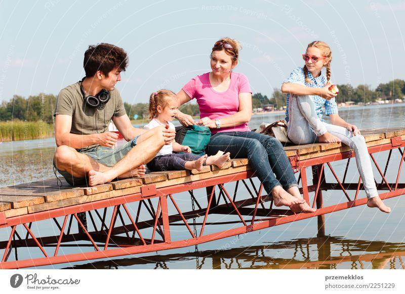 Eine Familie, die gemeinsam Urlaub macht und an einem sonnigen Sommertag einen Imbiss am Steg über dem See einnimmt Freude Glück Erholung Freizeit & Hobby
