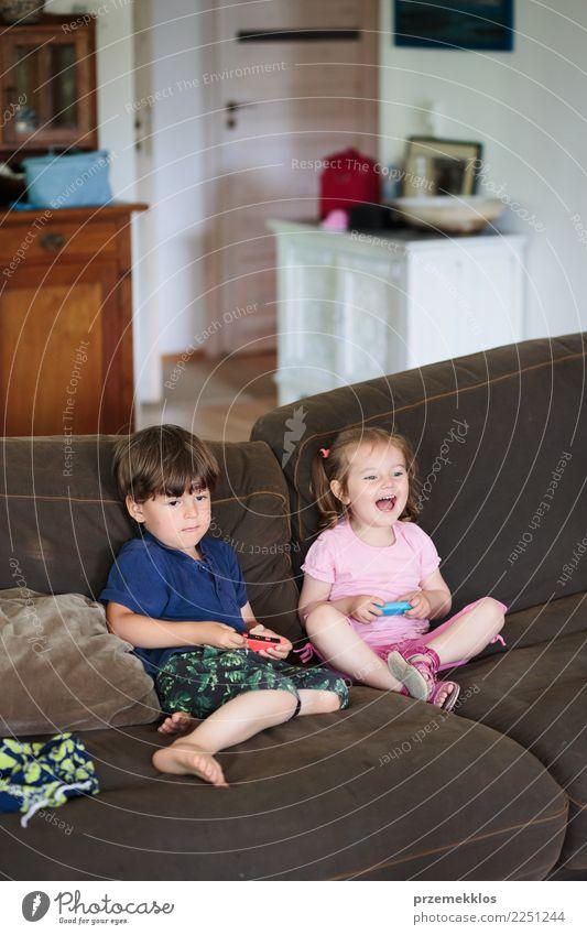 Kleinkindjunge und -mädchen, die das Videospiel zu Hause sitzt auf Sofa spielt Lifestyle Freude Glück Freizeit & Hobby Spielen Häusliches Leben Kind