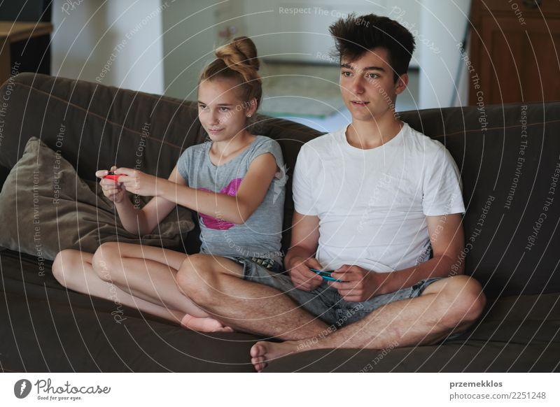 Junge und Mädchen, welche die Videospiele zu Hause sitzen auf Sofa spielt Lifestyle Freude Freizeit & Hobby Spielen Häusliches Leben Kind Technik & Technologie