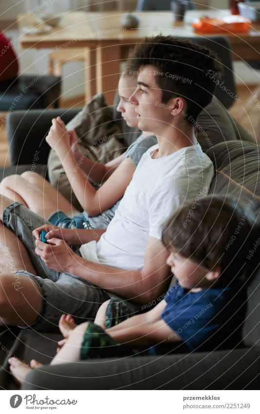 Junge und Mädchen, welche die Videospiele zu Hause sitzen auf Sofa spielt Lifestyle Freude Freizeit & Hobby Spielen Kind Technik & Technologie Kleinkind