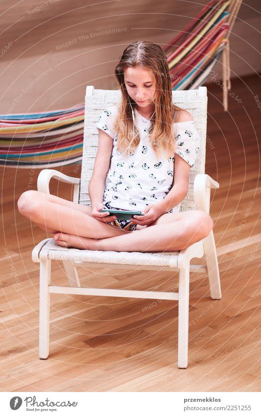 Mädchen, das Musik hört und mit Freunden am intelligenten Telefon plaudert Lifestyle kaufen Freizeit & Hobby Stuhl Kind Handy PDA Technik & Technologie Mensch