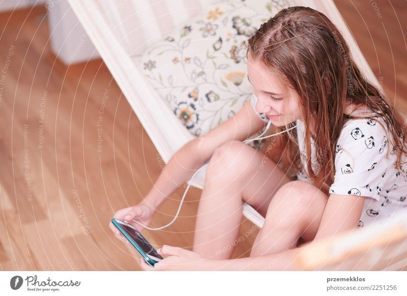 Mädchen, das Musik hört und mit Freunden auf Smartphone plaudert Lifestyle kaufen Freizeit & Hobby Kind Telefon Handy PDA Technik & Technologie Mensch