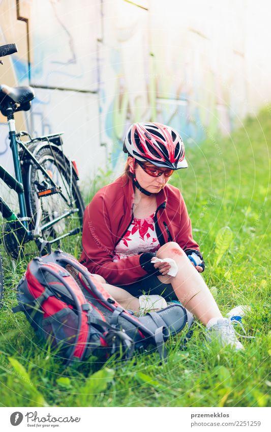 Frau, die die Wunde auf ihrem Knie mit Medizin im Spray ankleidet Lifestyle Ferien & Urlaub & Reisen Sommer Sport Fahrradfahren Mensch Erwachsene Gras Schmerz