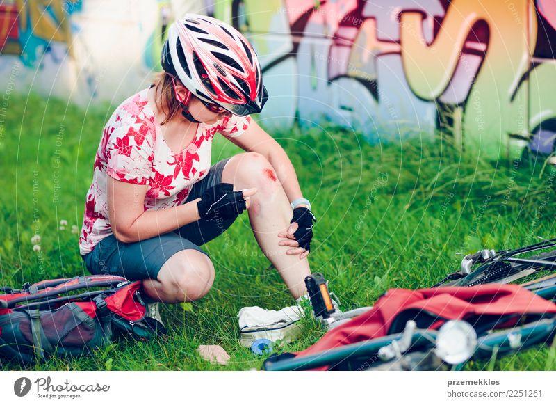 Frau, die die Wunde auf ihrem Knie mit Medizin im Spray ankleidet Lifestyle Ferien & Urlaub & Reisen Sommer Fahrradfahren Mensch Erwachsene 1 Gras Schmerz
