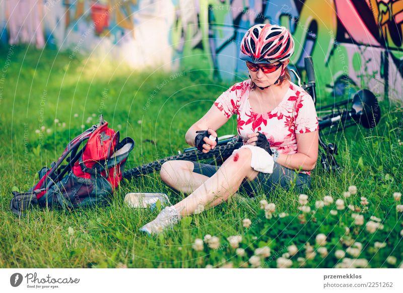 Frau, die die Wunde auf ihrem Knie mit Medizin im Spray ankleidet Lifestyle Ferien & Urlaub & Reisen Sommer Sport Fahrradfahren Mensch Erwachsene sitzen Unfall