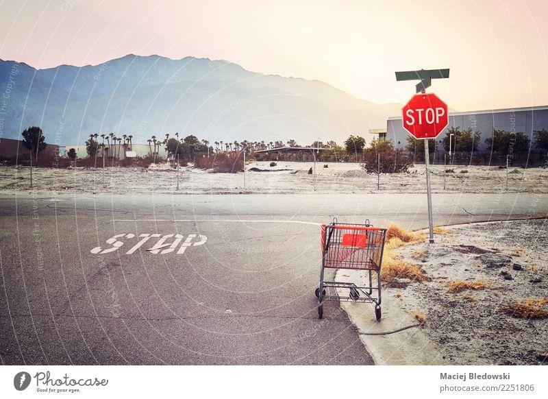Verlassener Einkaufswagen auf einer Straße bei Sonnenuntergang. kaufen Straßenkreuzung Wegkreuzung Autobahn retro trist Müdigkeit Zukunftsangst Unglaube