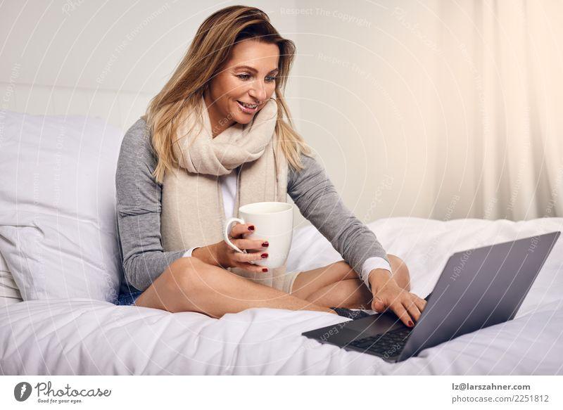 Attraktive Frau, die auf ihrem Bett mit Kaffee sitzt Tee Lifestyle kaufen Glück Zufriedenheit Schlafzimmer Arbeit & Erwerbstätigkeit Computer Notebook