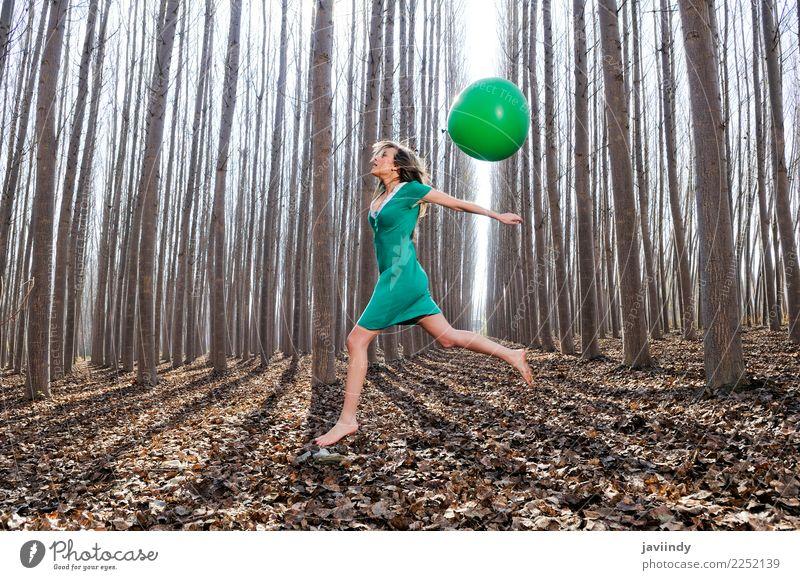 Blondes Mädchen, das in das Holz mit einem Ballon springt Lifestyle Freude schön Erholung Mensch Frau Erwachsene Natur Herbst Baum Blatt Park Wald blond
