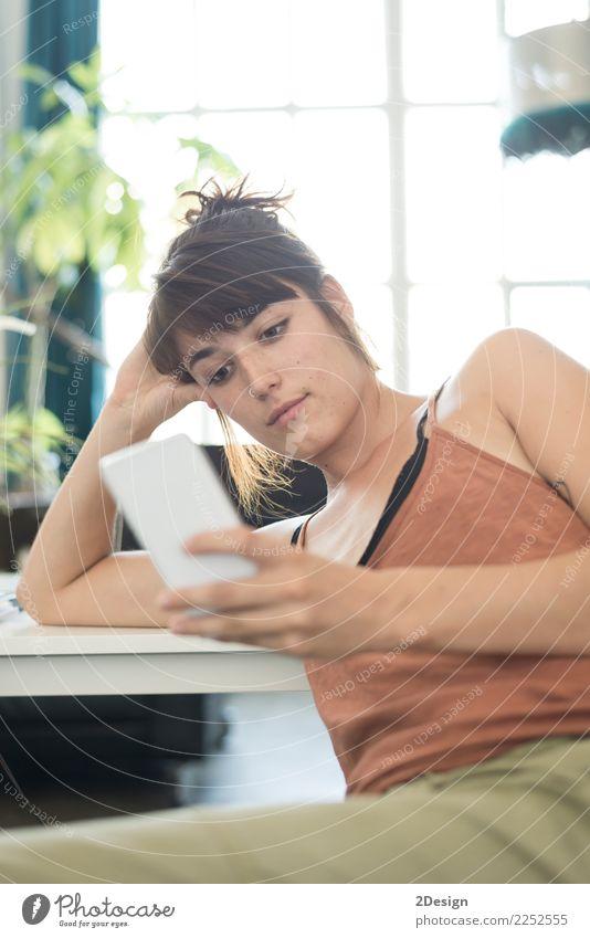 Glückliche junge Geschäftsfrau, die Handy im Büro verwendet Frau Mensch Erwachsene Lifestyle Business Arbeit & Erwerbstätigkeit Technik & Technologie sitzen