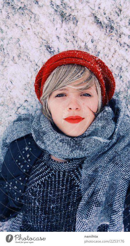 Junge Frau, die sich über dem Schnee am Winter hinlegt Lifestyle Stil schön Haut Gesicht Wellness Ferien & Urlaub & Reisen Abenteuer Winterurlaub Mensch feminin