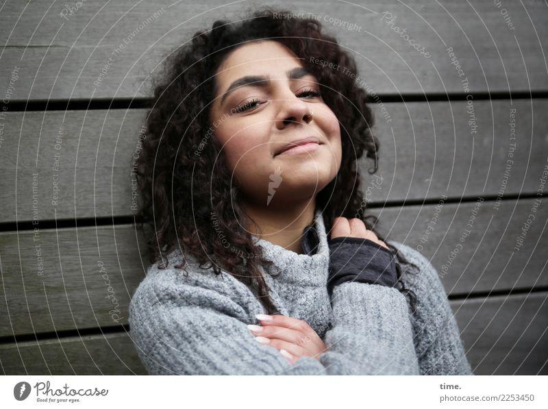 Nikolija feminin Frau Erwachsene 1 Mensch Mauer Wand Pullover Piercing schwarzhaarig langhaarig Locken Holz beobachten festhalten Lächeln Blick Freundlichkeit