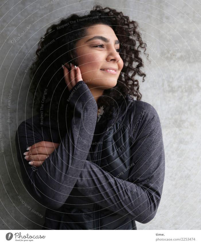 Nikolija feminin Frau Erwachsene 1 Mensch Mauer Wand Pullover Haare & Frisuren brünett langhaarig Locken Erholung festhalten Lächeln lachen Blick stehen