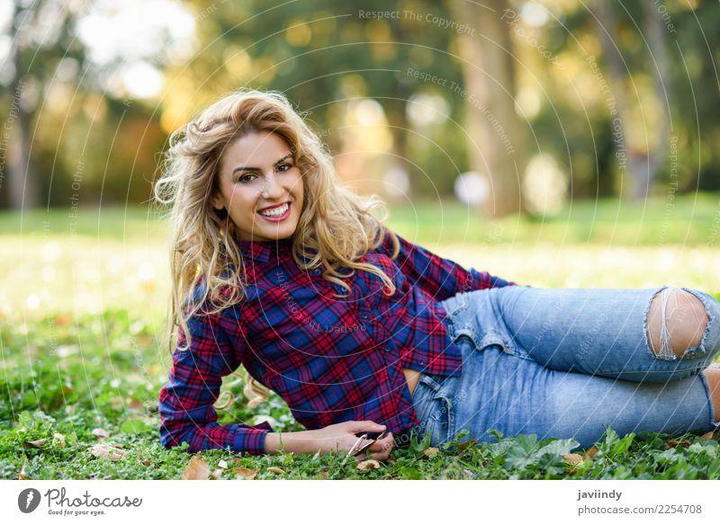 Frau, die auf dem Gras eines städtischen Parks lächelt Mensch Natur Jugendliche Junge Frau schön weiß Erholung Freude 18-30 Jahre Erwachsene Lifestyle Herbst