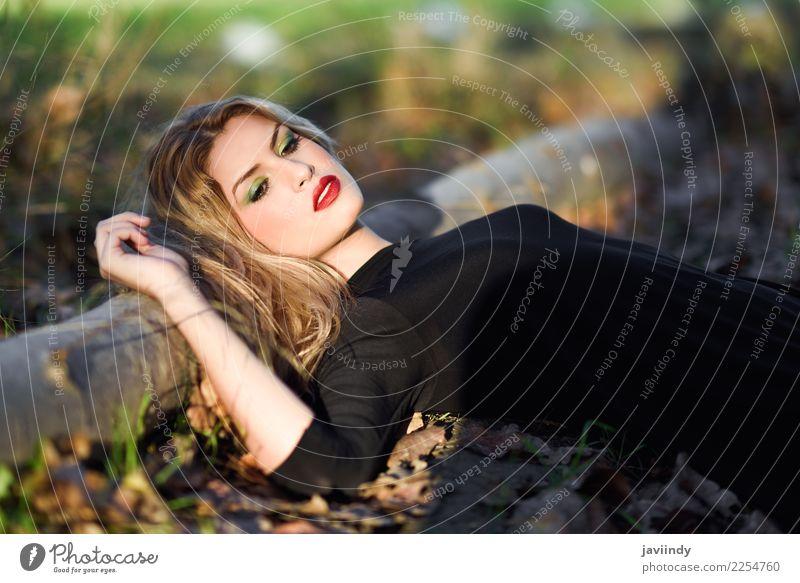 Entspanntes Mädchen, das auf dem Feld mit dem langen lockigen Haar liegt schön Haare & Frisuren Gesicht Schminke Mensch feminin Junge Frau Jugendliche