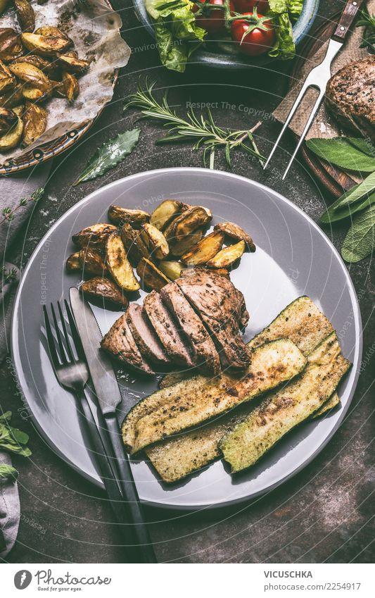 Essen mit gebratenem Fleisch, Bratkartoffeln und Gemüse Lebensmittel Ernährung Mittagessen Abendessen Bioprodukte Geschirr Teller Besteck Stil Design Restaurant