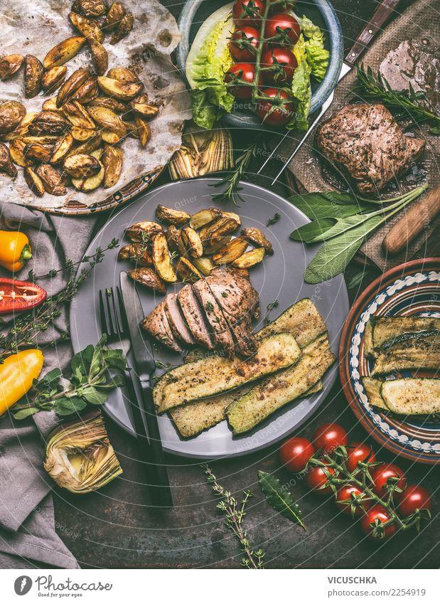Essen mit gebratenem Fleisch, Bratkartoffeln und Gemüse Lebensmittel Salat Salatbeilage Ernährung Mittagessen Abendessen Bioprodukte Geschirr Teller Besteck