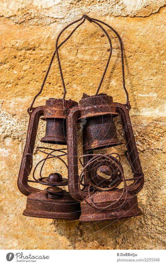 Zwei vergessene alte Laternen hängen gemeinsam an der Wand und erinnern sich an alte Zeiten. Tag Menschenleer Außenaufnahme Farbfoto Antiquität Öllampe Lampe