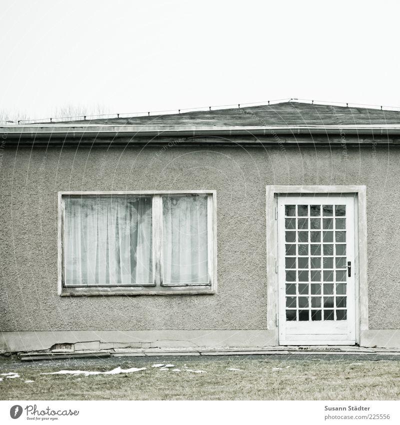 Datschenclique alt Haus Fenster Wiese Schnee grau Tür kaputt trist verfallen Vergangenheit DDR Einfamilienhaus Eingangstür Holztür