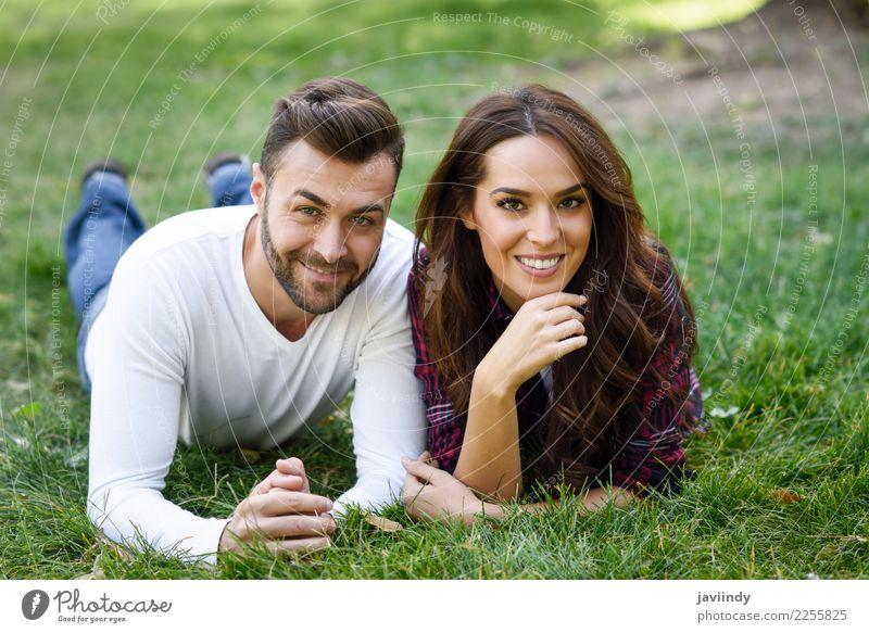 Schöne junge Paare, die auf Gras in einem städtischen Park legen Frau Mensch Natur Jugendliche Mann Junge Frau Sommer schön grün Junger Mann Freude 18-30 Jahre