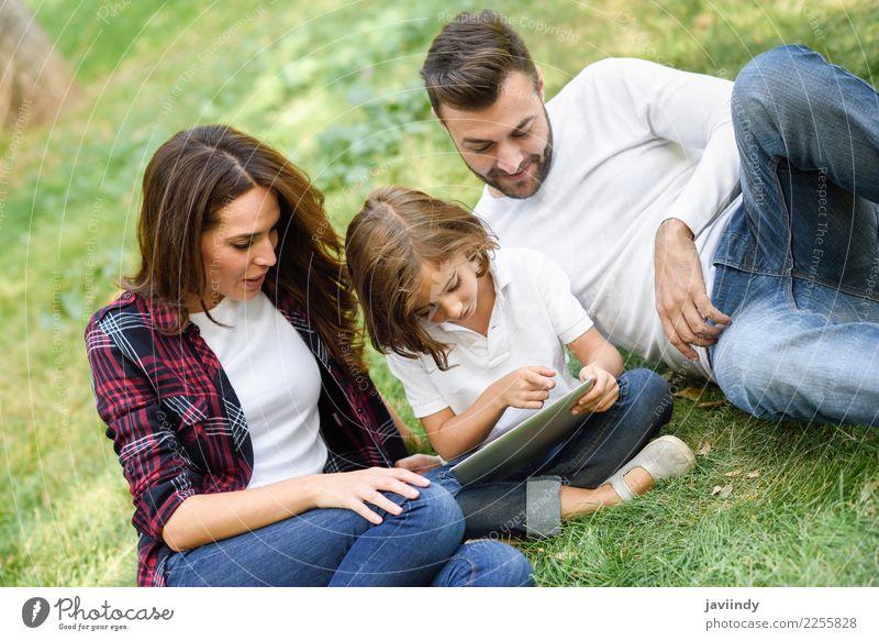Glückliche Familie in einem städtischen Park, der mit Tablettencomputer spielt Kind Frau Mensch Jugendliche Mann Junge Frau Sommer schön Junger Mann Freude