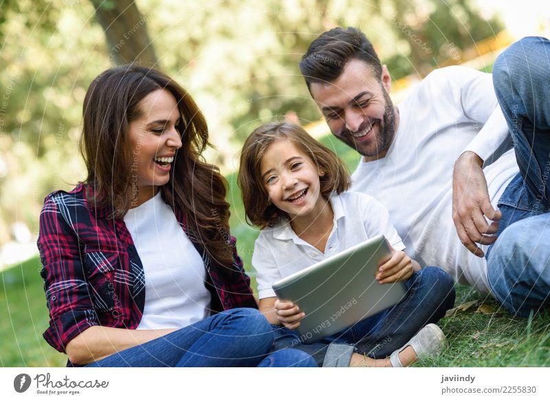 Glückliche Familie in einem städtischen Park, der mit Tablet-Computer spielt Kind Frau Mensch Jugendliche Mann Junge Frau Sommer schön Junger Mann Freude