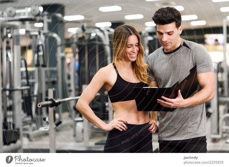 Persönlicher Trainer und Kunde, die seinen Fortschritt an der Turnhalle betrachten Frau Mensch Jugendliche Mann Junge Frau Junger Mann weiß 18-30 Jahre