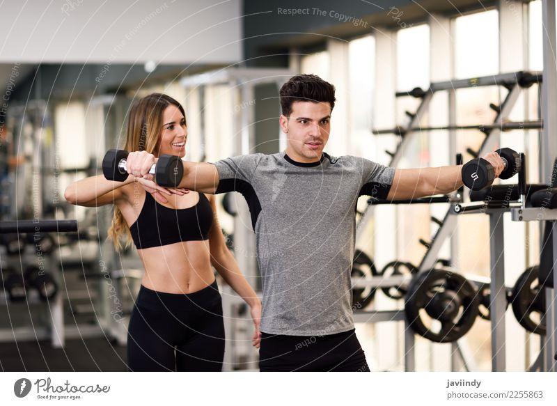 Weiblicher persönlicher Trainer, der einem jungen Mann hilft, Hanteln anzuheben Trainerin Sporthalle Frau Fitness Lifestyle verschlissen üben Gewichte