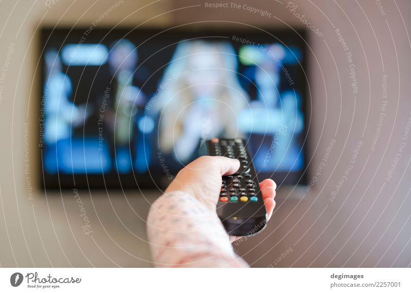 TV und Hand halten Fernbedienung. Mensch Erholung Leben Freizeit & Hobby Technik & Technologie beobachten Medien heimwärts Fernsehen Kontrolle Bildschirm