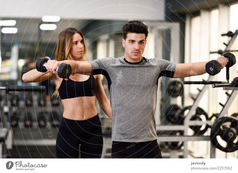 Weiblicher persönlicher Trainer, der einem jungen Mann hilft, Hanteln anzuheben Frau Mensch Jugendliche Junge Frau Junger Mann weiß 18-30 Jahre Erwachsene