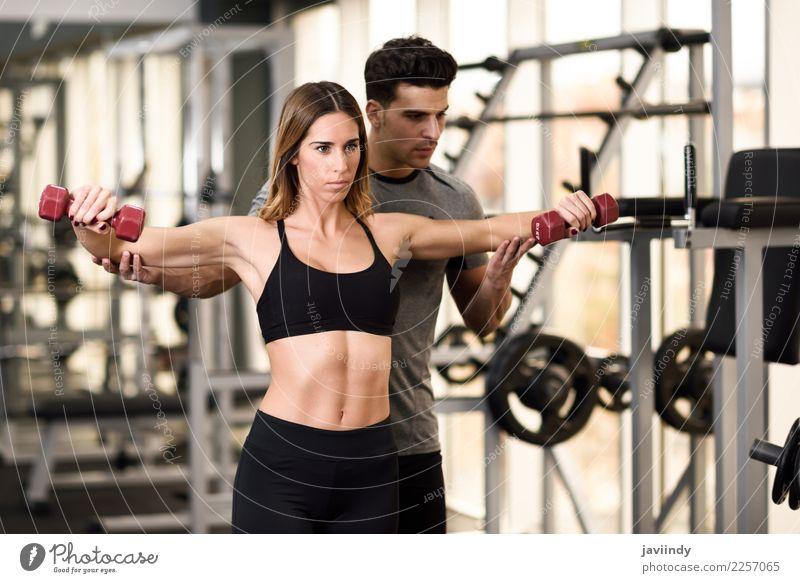 Persönlicher Trainer, der einer jungen Frau hilft, humbells zu heben Mensch Jugendliche Mann Junge Frau Junger Mann weiß 18-30 Jahre Erwachsene Lifestyle Sport