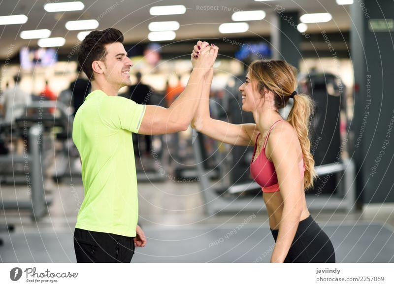 Lächelnder junger Mann und Frau, die Hoch fünf in der Turnhalle tun Mensch Jugendliche Junge Frau Junger Mann 18-30 Jahre Erwachsene Lifestyle Sport feminin