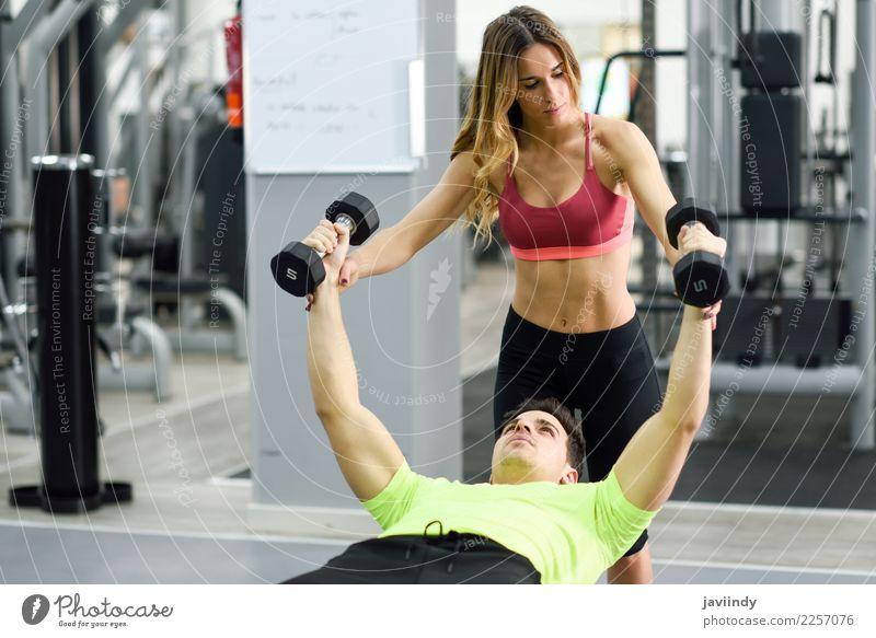 Weiblicher persönlicher Trainer, der einem jungen Mann hilft, Gewichte zu heben Frau Mensch Jugendliche Junge Frau Junger Mann weiß 18-30 Jahre Erwachsene