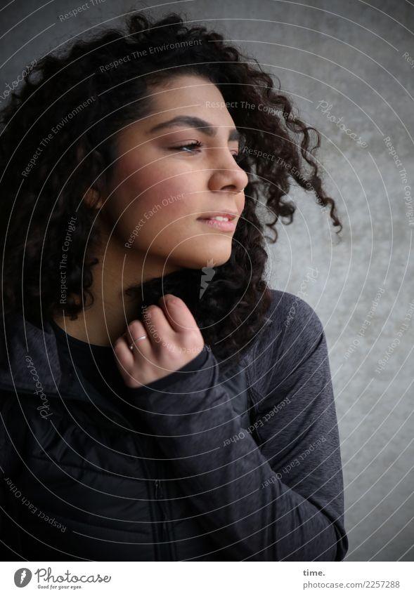 Nikolija feminin Frau Erwachsene 1 Mensch Mauer Wand Jacke Haare & Frisuren brünett langhaarig Locken beobachten festhalten Blick dunkel Freundlichkeit schön