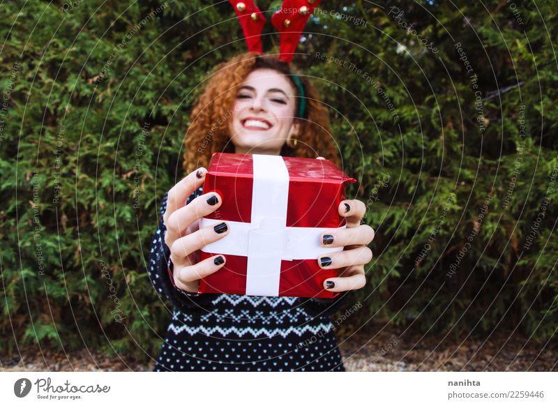 Junge Frau, die ein Weihnachtsgeschenk hält Mensch Natur Jugendliche Weihnachten & Advent Baum Freude Winter 18-30 Jahre Erwachsene Lifestyle feminin Stil Glück
