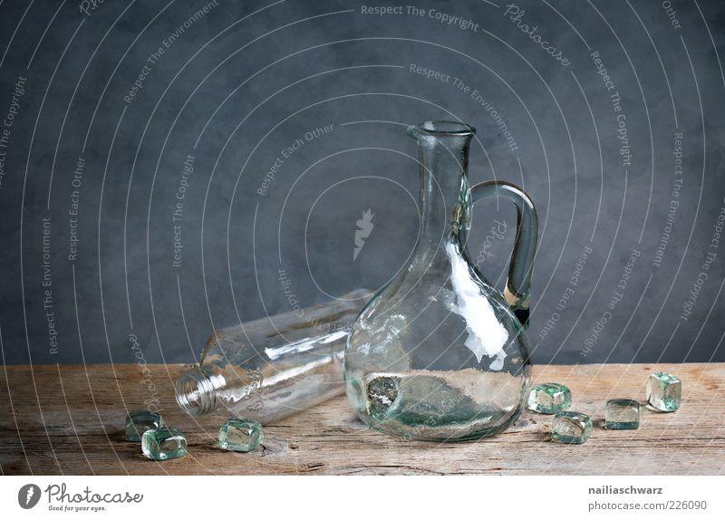 Stilleben mit Glas blau grau braun glänzend Glas ästhetisch Sauberkeit Klarheit Flasche Stillleben Würfel Reinheit Holztisch umgefallen