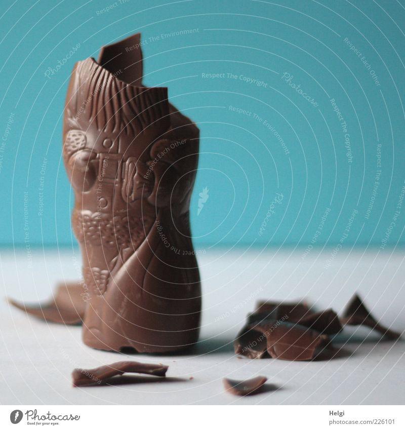 angeknabberter Schokoladenweihnachtsmann auf einem weißen Tisch und blauer Wand Lebensmittel Süßwaren Ernährung liegen stehen authentisch einfach kaputt klein