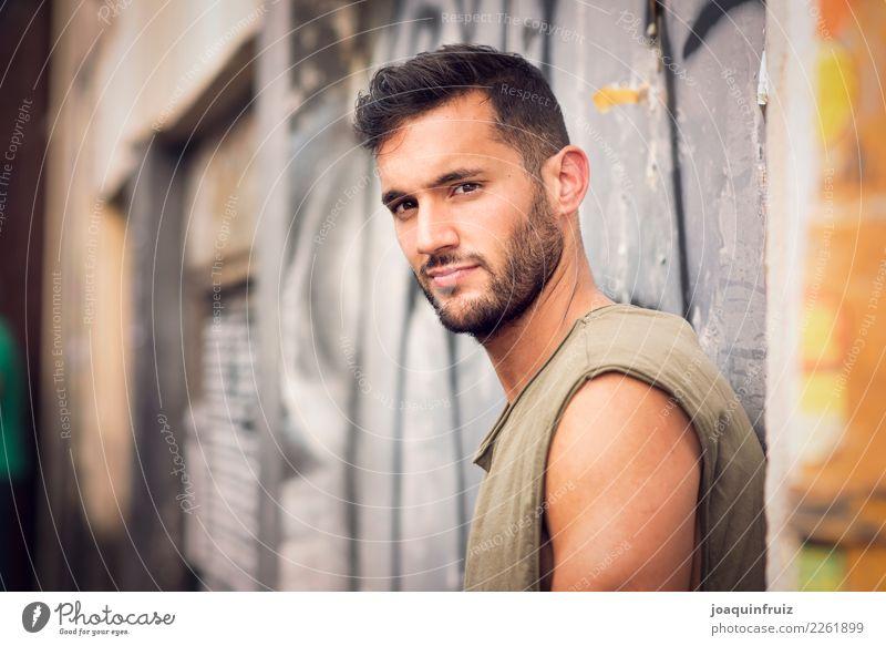 junger hübscher Mann mit T-Shirt gegen eine Wand in der Straße Lifestyle Stil Glück Mensch Junge Erwachsene Stadt Mode Jeanshose Coolness trendy modern weiß Typ
