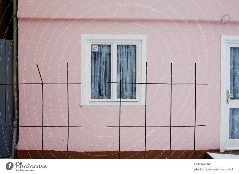 Haus hinter Draht Einfamilienhaus Bauwerk Gebäude Architektur Mauer Wand Fassade Fenster Stimmung bescheiden Zaun Drahtzaun Gardine Tür Eingang Vorderseite rosa