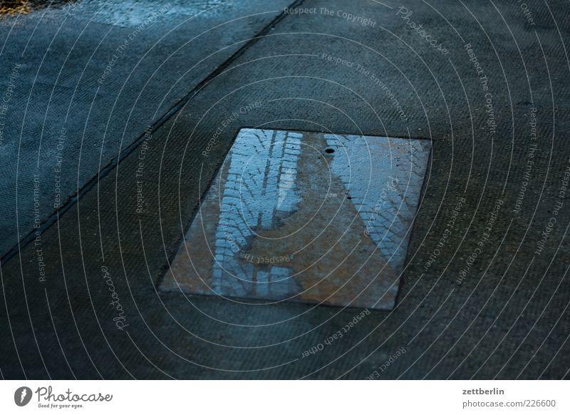Überfahrenes Eisen dunkel Wand Gefühle Mauer Metall glänzend nass Beton Platz trist Bauwerk Asphalt Spuren Stahl Rost Reifenprofil