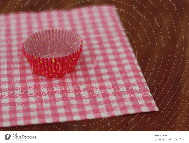 Pinke Cupcake Form aus Papier liegt auf einer rosa-weiß karierten Serviette. Süß, kitschig. Dekoration & Verzierung Holz Muffin Kitsch rot-weiß Tischplatte leer