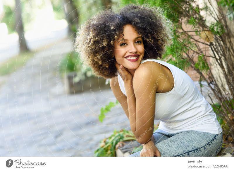 Gemischte Frau mit Afro-Frisur lächelnd im Stadtpark Lifestyle Stil Glück schön Haare & Frisuren Gesicht Mensch feminin Junge Frau Jugendliche Erwachsene 1