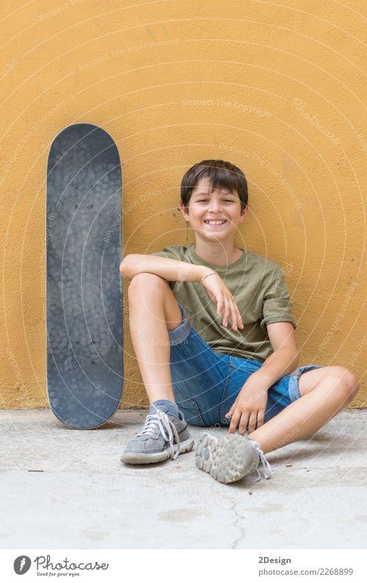 Ein lächelnder Junge mit dem Skateboard, das alleine auf dem Fußboden sitzt Lifestyle Freude Erholung Freiheit Sommer Sonne Kind Handy PDA Mensch Mann