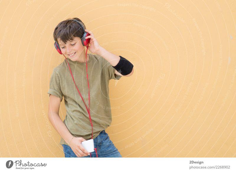 Hübsches jugendlich, ein grünes T-Shirt tragend, das Musik hört Lifestyle Stil Freude Glück Telefon Headset PDA Technik & Technologie Mensch Junge Mann